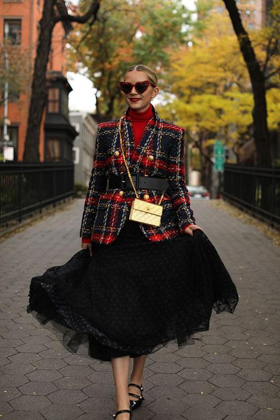 Set đồ thu đông bắt mắt với tông đỏ đen được xây dựng bởi áo len cổ lọ, áo khoác caro và chân váy chấm bi.