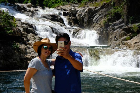 Lưu giữ lại những khoảnh khắc gia đình bên dòng thác Yang Khang thiêng liêng. - Ảnh: ĐÌNH CƯƠNG