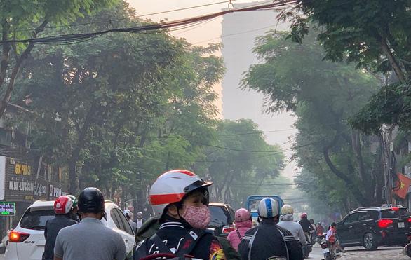 """Sáng 12-11, gần như mọi người ra đường ở Hà Nội đều phải mang khẩu trang khi ô nhiễm không khí lên tới ngưỡng nguy hại; đường phố, đặc biệt khu nhà cao tầng có hiện tượng như """"sương mù"""" đặc quánh - Ảnh: XUÂN LONG"""