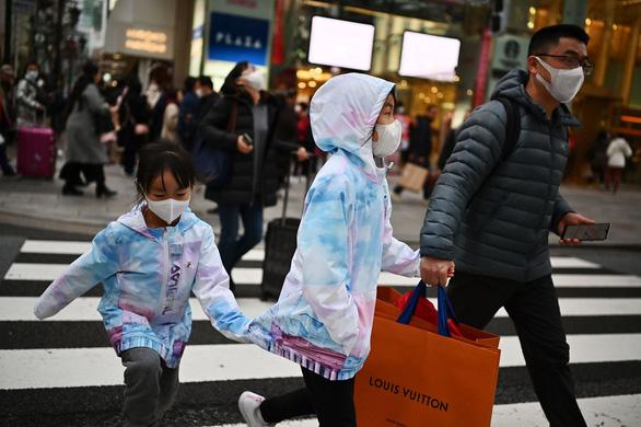 Khách mua hàng cẩn thận đeo khẩu trang ở khu Ginza ở Tokyo (Nhật) - Ảnh: AFP