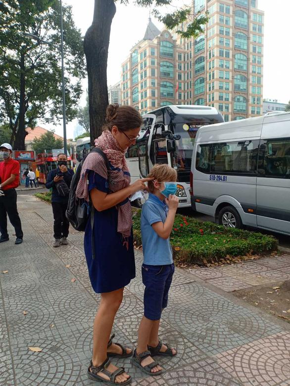 Một du khách nước ngoài vội đeo khẩu trang cho con trai ngay khi được tặng - Ảnh: N.BÌNH
