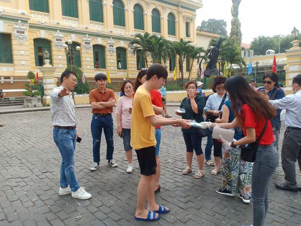 Du khách nước ngoài nhận khẩu trang miễn phí từ các tình nguyện viên - Ảnh: N.BÌNH