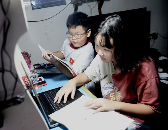 Hai chị em Khánh Giang, lớp 8 Trường THCS Đoàn Thị Điểm và Duy Khánh, lớp 3 Trường tiểu học Trương Quyền (quận 3, TP.HCM) học bài ở nhà trong thời gian nghỉ học - Ảnh: TỰ TRUNG
