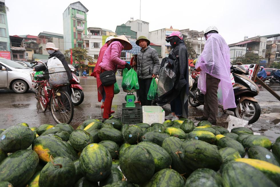 """Bất chấp thời tiết mưa rét, rất nhiều người dân đã tới ủng hộ một điểm """"giải cứu"""" dưa hấu trên đường Giải Phóng - Ảnh: CHÍ TUỆ"""