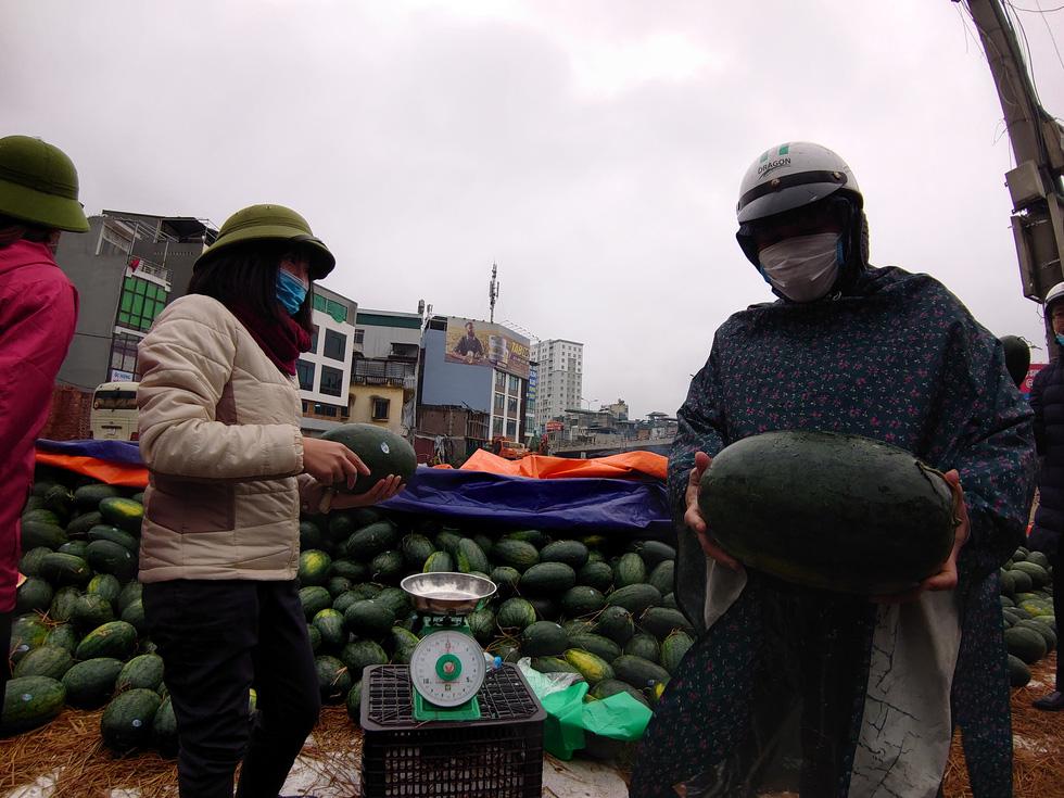 Mỗi người dân mua 1-2 quả dưa để ủng hộ thương lái - Ảnh: NAM TRẦN