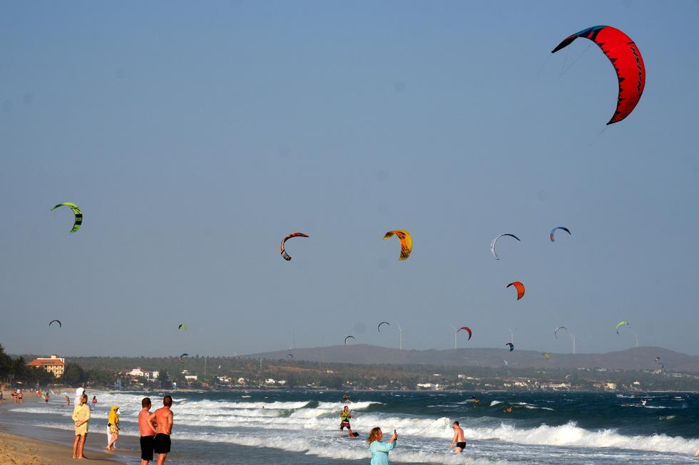 Mũi Né là địa điểm quen thuộc của những người yêu thích các môn thể thao lướt ván nhờ hội tụ nhiều yếu tố như bãi biển đẹp, gió lớn, eo biển có sóng phù hợp để lướt ván. Những ngày nắng đẹp và có gió, những eo biển ở Mũi Né thường rợp bóng diều lướt ván. Ngày 15-3, dù tình hình dịch COVID-19 đang diễn biến phức tạp nhưng cũng không hề khiến bãi biển vắng người chơi lướt ván - Ảnh: SƠN LÂM