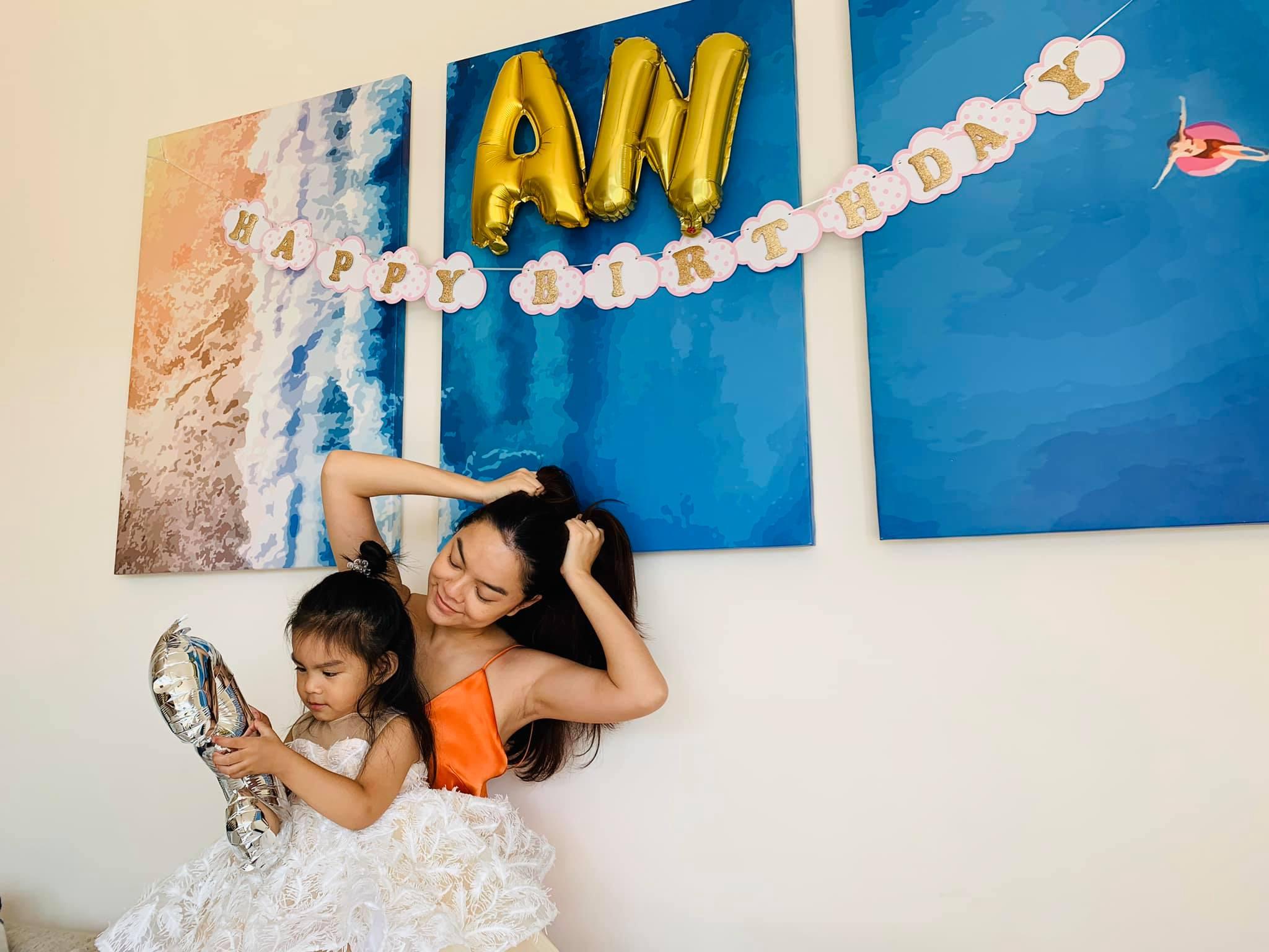 """Vì dịch bệnh đang hoành hành nên nữ ca sĩ chỉ tổ chức tiệc mừng tại nhà. Giọng ca """"Bụi bay vào mắt""""diện đầm hai dây màu cam, chụp hình cùng con."""