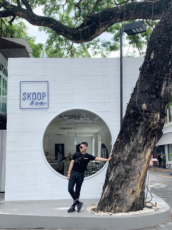 """Skoop & Co gây ấn tượng với những khung cửa sổ hình tam giác, hình tròn và tông màu trắng chủ đạo. Bên trong rộng, thoáng. Chỉ có một tầng, nhưng quán có view đường phố khá đẹp và xung quanh có nhiều quán cà phê xinh xắn. Gốc cây trước cửa quán trở thành """"người bạn"""" quen thuộc của thực khách."""