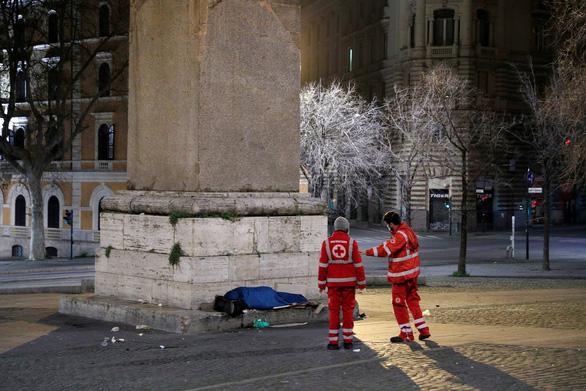 Nhân viên Hội Chữ thập đỏ ở Ý kiểm tra một người vô gia cư ở Rome - Ảnh: REUTERS