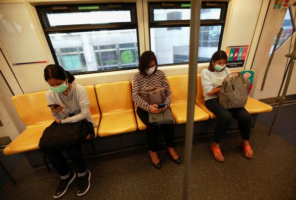 Hành khách đeo khẩu trang và ngồi cách nhau một ghế theo khuyến cáo y tế về phòng dịch COVID-19 của Bộ Y tế Thái Lan khi đi phương tiện giao thông công cộng ở Bangkok - Ảnh: REUTERS