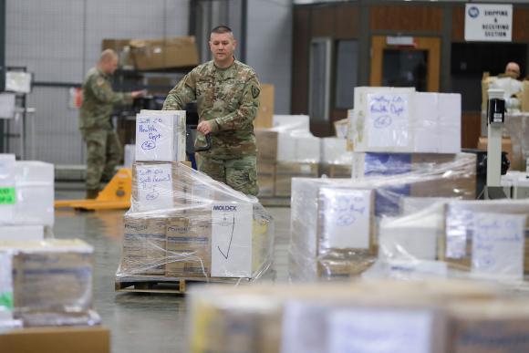 Một Vệ binh Quốc gia Indiana xếp hàng một pallet các vật tư y tế ở Indianapolis vào thứ Năm ngày 26/03 - Ảnh: AP