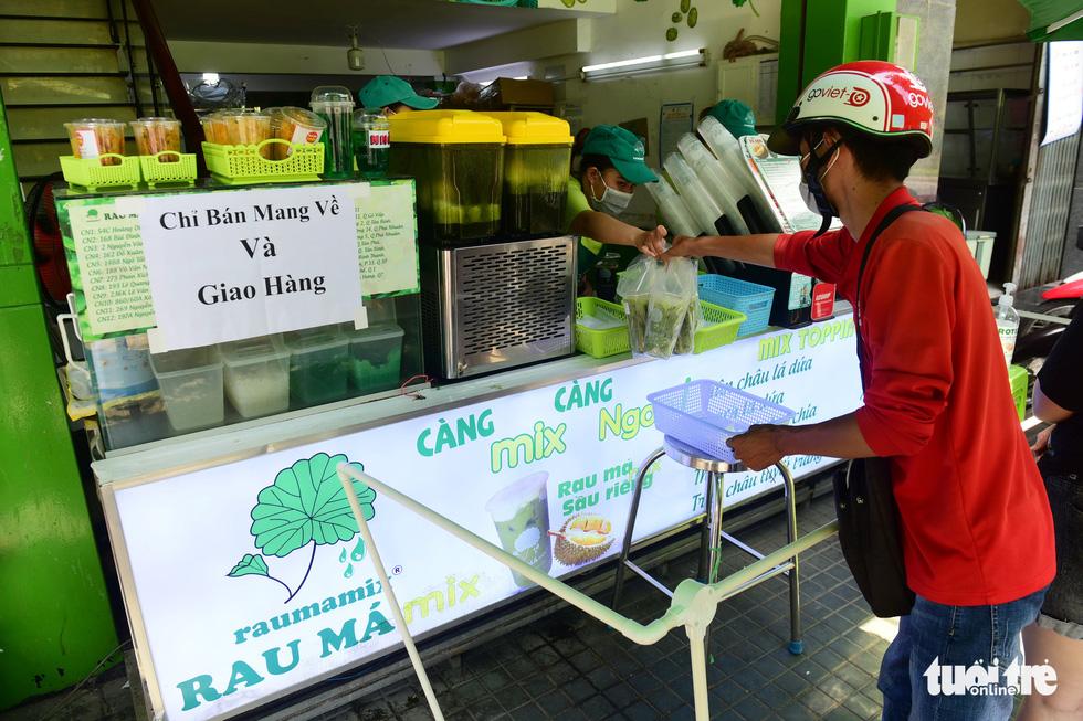 Một quán nước rau má trên đường Phan Xích Long, quận Phú Nhuận, TP.HCM lắp đặt hàng rào cách xa 2m và chỉ bán mang về - Ảnh: QUANG ĐỊNH