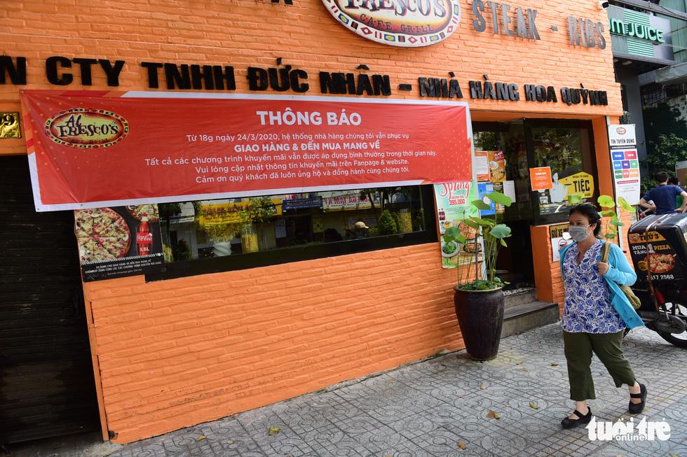 Một cửa hàng pizza trên đường Phan Xích Long, quận Phú Nhuận, TP.HCM thông báo phục vụ giao hàng và đến mua mang về - Ảnh: QUANG ĐỊNH