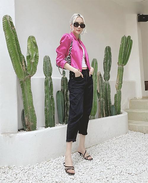 Áo jacket dáng lửng được Thiều Bảo Trang chọn làm điểm nhấn cho set đồ trẻ trung với áo hở eo, quần jeans xắn gấu, sandal và shoulder bag.