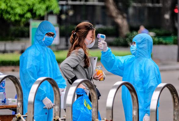 Nhân viên y tế đo thân nhiệt người đi vào Bệnh viện Bạch Mai, Hà Nội trước khi bệnh viện được cách ly (ảnh chụp sáng 29-3) - Ảnh: NAM TRẦN