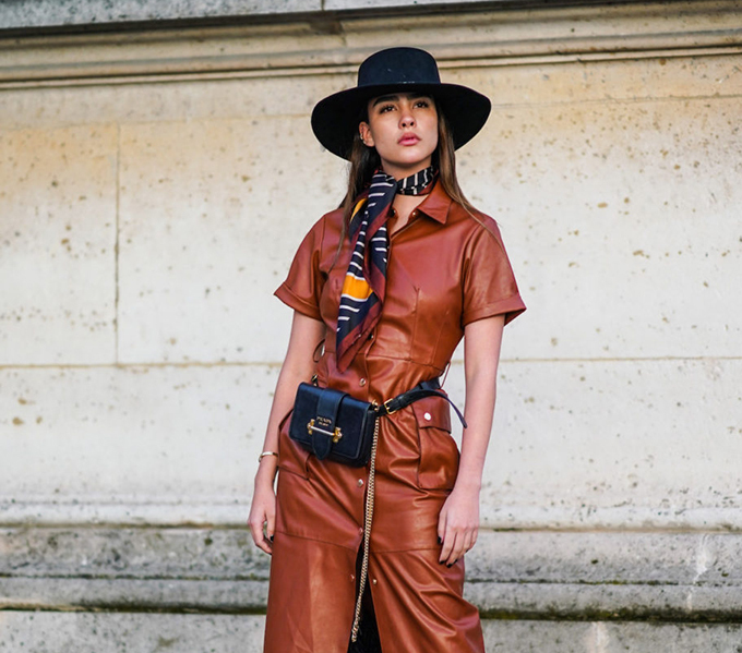 PARIS, FRANCE - OCTOBER 01: A guest wears a hat, a colored scarf, a brown leather dress, a Prada belt bag with a golden chain, fluffy black pants, outside Louis Vuitton, during Paris Fashion Week - Womenswear Spring Summer 2020, on October 01, 2019 in Paris, France. (Photo by Edward Berthelot/Getty Images)